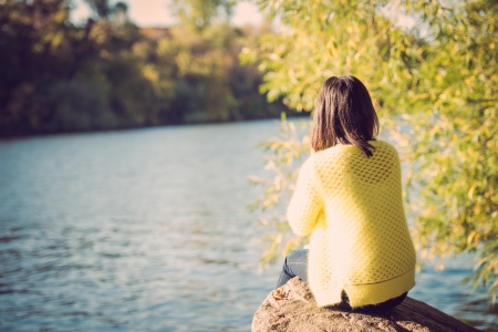 Attractive lonely young woman sitting on a rock next to river looking upset Stock Photo