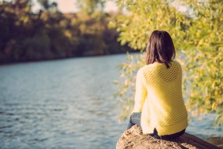 Aantrekkelijke eenzame jonge vrouw zitten op een rots naast de rivier op zoek boos