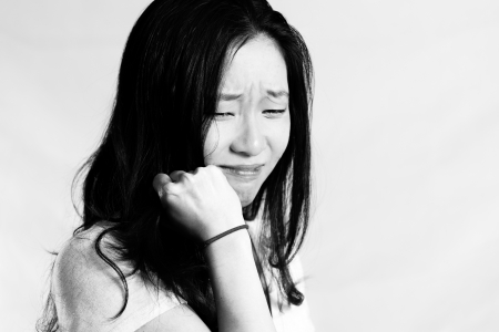 Portrait of young woman crying while pulling her hair, black and white style