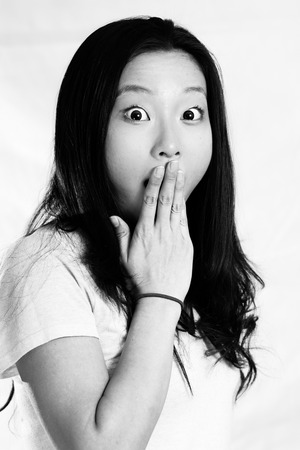 Portrait of young woman looking shocked and covering her mouth, black and white style photo