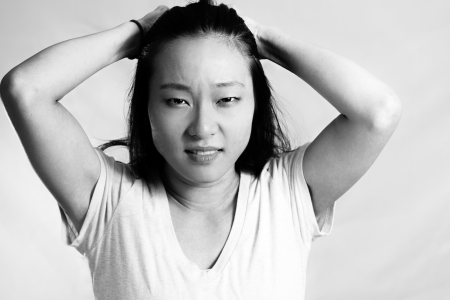 Portrait of young woman pulling her hair in frustration, black and white style photo