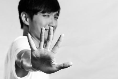 deny: Young man holding up his hand and refusing, black and white style