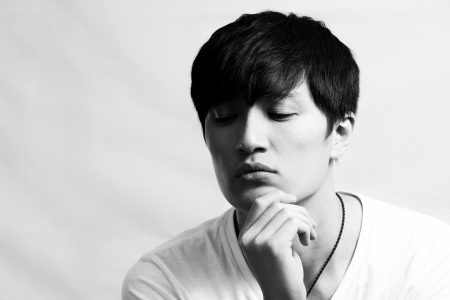 Portrait of handsome young man looking deep in thought, black and white style Stock Photo