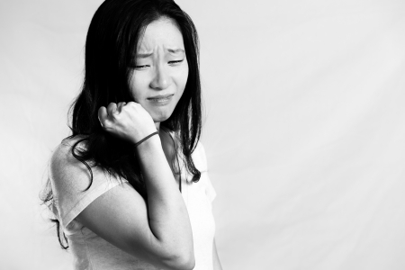 Portrait of young woman crying while pulling her hair, black and white style photo