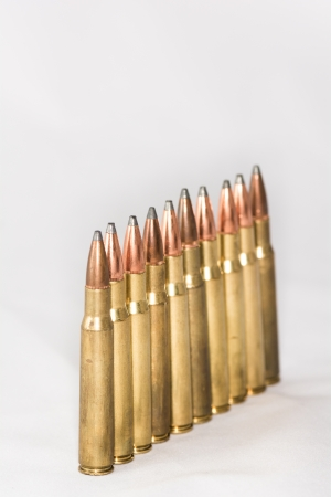 A few rifle bullets lined up in a row on white background Stock Photo - 23921427
