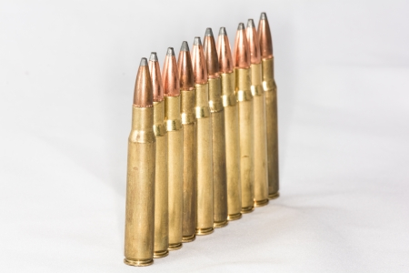 A few rifle bullets lined up in a row on white background Stock Photo - 23921432
