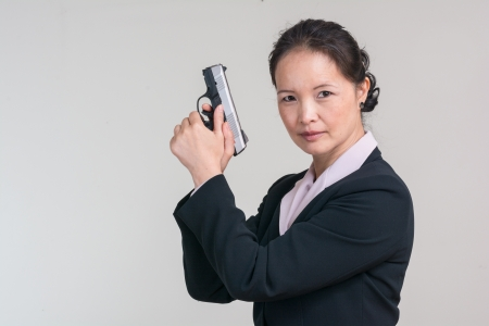 Portrait of woman in business suit holding a hand gun with agent pose on grey background Banco de Imagens
