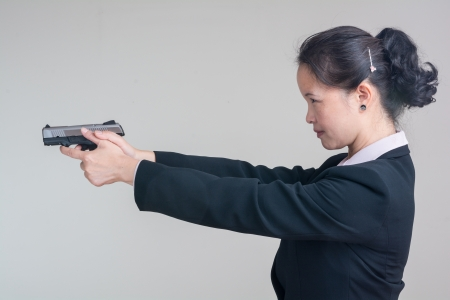 Portrait of woman in business suit aiming a hand gun on grey background Banco de Imagens