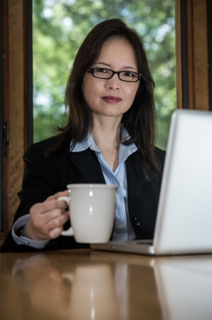 front desk: Woman in business suit with laptop on desk and picking up coffee in front of a window Stock Photo
