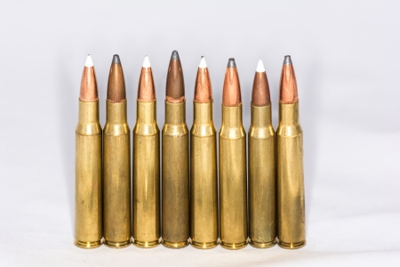 A few rifle bullets lined up in a row on white background photo