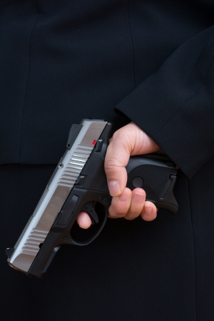 Close up with woman in business suit hold a pistol to dark suit  photo