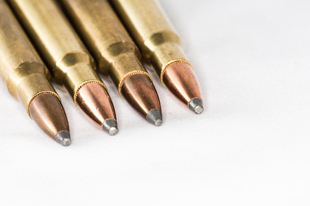 Tips of a few rifle bullets lined up in a row on white background photo
