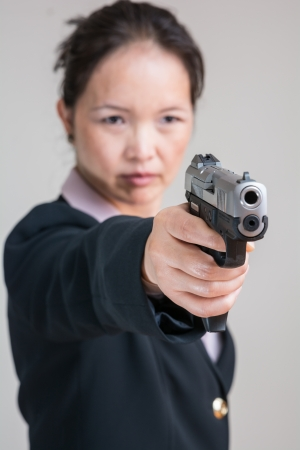 Close up portrait of woman in business suit aiming a hand gun Stock Photo