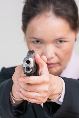 Close up portrait of woman in business suit aiming a hand gun at you Banco de Imagens