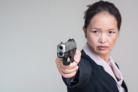 Close up portrait of woman in business suit aiming a hand gun Banco de Imagens