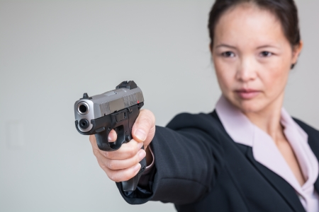 gun barrel: Close up portrait of woman in business suit aiming a hand gun Stock Photo