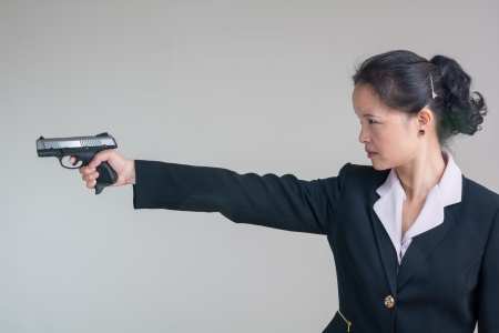sleeve: Portrait of woman in business suit aiming a hand gun on grey background Stock Photo