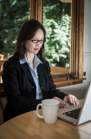 front desk: Woman in business suit with laptop and coffee on desk in front of a window Stock Photo