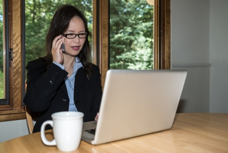 front desk: Woman in business suit with laptop and coffee on desk making a phone call in front of a window