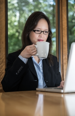 Woman in business suit with laptop on desk and drinking coffee in front of a window photo