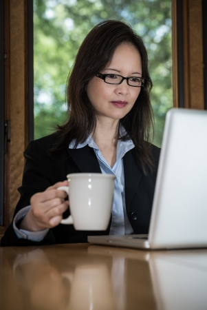 Woman in business suit with laptop on desk and picking up coffee in front of a window photo