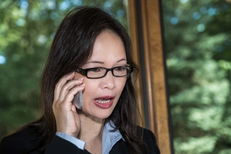 Woman in business suit speaking on a cellphone in front of a window looking upset photo