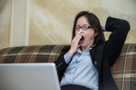 Woman in business suit feeling tired and yawning on sofa with labtop photo