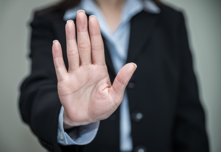 denying: Professional woman in business suit shaking one hand and denying on grey background