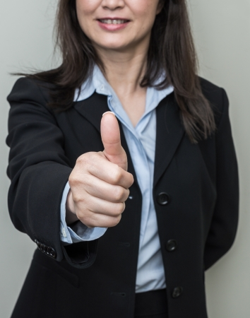 Professional woman in business suit giving thumbs up in approval on grey background