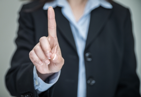 denying: Professional woman in business suit shaking one finger and denying on grey background  Stock Photo