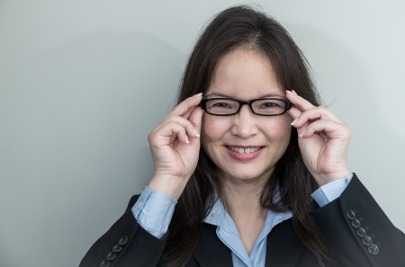 account executive: Portrait of woman with glasses in business suit smiling on grey background  Stock Photo