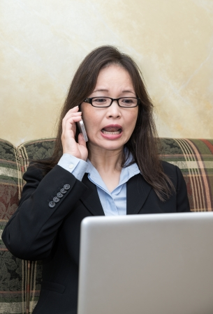 Professional woman in business suit yelling on a cell phone while looking at laptop photo