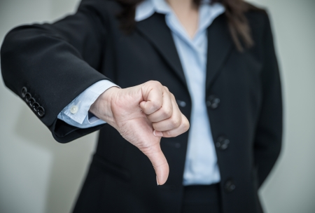 disapproval: Professional woman in business suit giving thumbs down in disapproval on grey background  Stock Photo