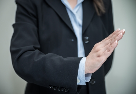 Professional woman in business suit signals denial with one hand on grey background  Stock Photo