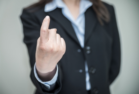 come in: Professional woman in business suit signals come here on grey background  Stock Photo