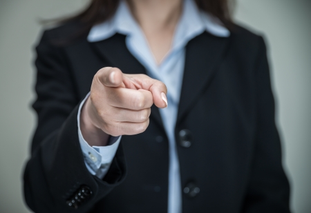 Professional woman in business suit pointing at you with one finger on grey background  Stock Photo