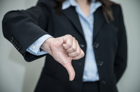Professional woman in business suit giving thumbs down in disapproval on grey background  Stock Photo