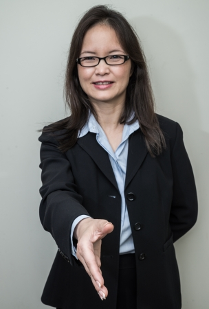Professional woman in business suit ready for hand shake with grey background
