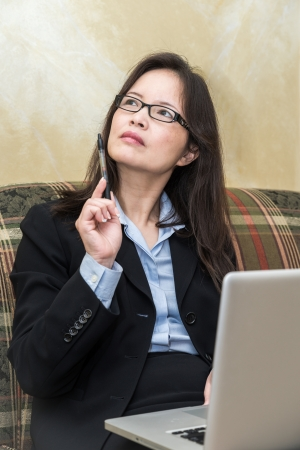 Professional woman in business suit on sofa in deep thought with pen and laptop  photo