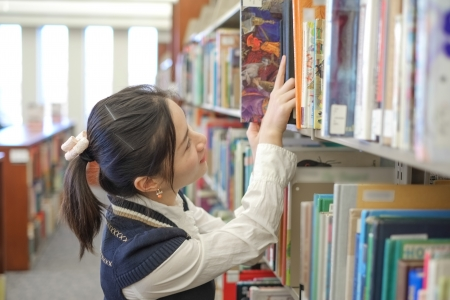 Smart female student picking and taking a book from a library shelf Stock Photo