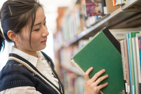 grabbing at the back: Young female student putting a green book back onto a bookshelf in library