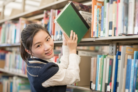 Portrait of young female student taking a green book from a bookshelf in library photo