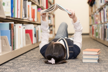 Young girl student laying on the library floor and reading a stack of books