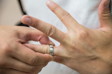fingers: Man pulling a wedding ring off from his finger