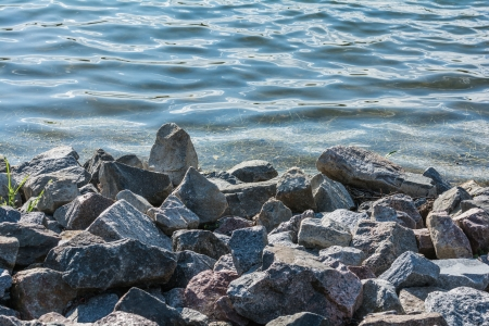 Pile of rocks at lakeside forming a natural beach photo