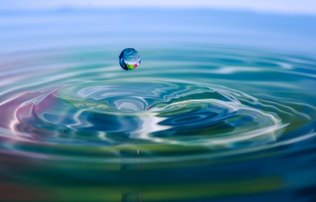 source: Instant of a drop of water hitting water surface and causing a small splash