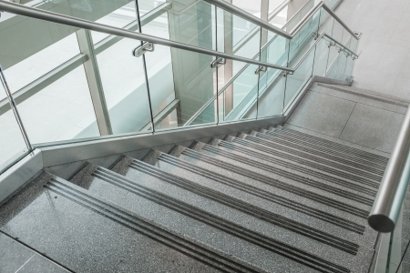 stone stairs: Pattern of several steps of granite stairs with glass railing Stock Photo