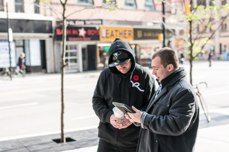 TORONTO, ON, CANADA - OCTOBER 30:  Two tourist talking about directions on Young Street, in Toronto Canada on October 30, 2013
