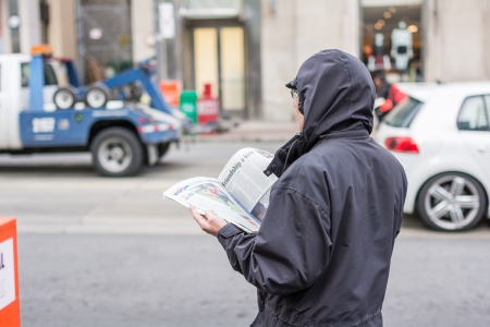 TORONTO, ON, CANADA - OCTOBER 30: Man in coat reading news paper on the side of a street, in Toronto Canada on October 30, 2013 Editorial