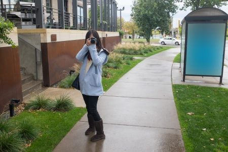 Girl photographer with camera on a public side walk during autumn listening to music